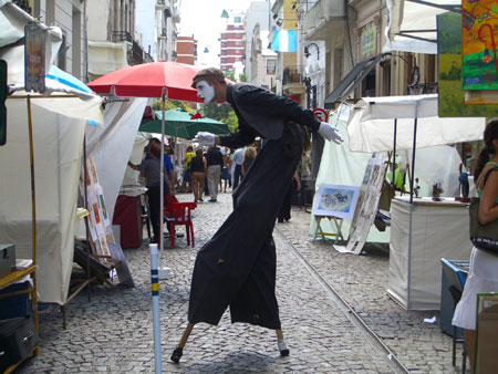 A mime browses the San Telmo art fair on a Sunday.
